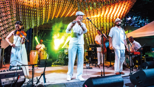 Doug Little '91 plays flute on stage with the rest of the members of his band, Charanga Tropical