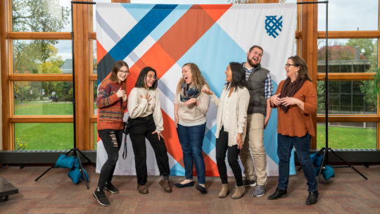 Photo of people laughing in front of a Macalester backdrop.