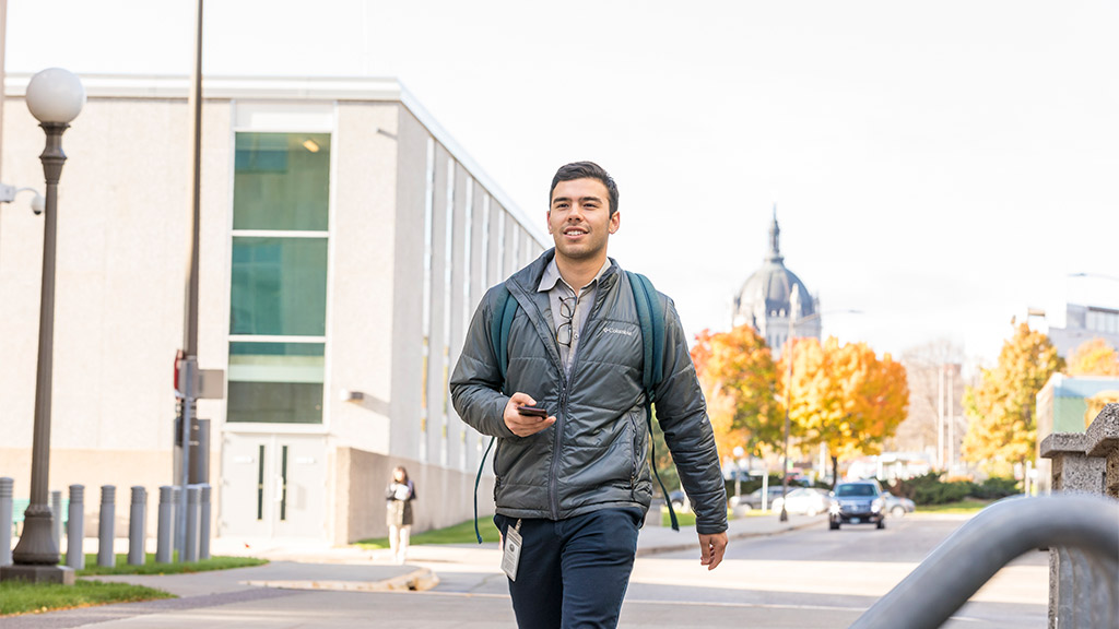 Student Jack Fong Gougoutas walking in front of the Minnesota State Capitol.